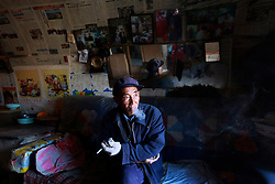 Chinese apple farmer Cui Weiliang, 66, smokes in his 'yaodong' or cave home on the top of a mountain in Yichuan county of Yan'an city, Shaanxi Province China, 06 November 2012. Cui makes about 10,000 to 20,000 RMB (2,495 euros) a year from his produce from the 4mu (around 2666 square metres) of land allocated to him. His children have all left the mountains to find work. The 'yadong' or cave dwellings are typical in the plateaus of northern China in Shaanxi Province where many of Yan'an's rural population still live in. They are mostly carved out from the yellow earth of the Loess hillsides and are about seven to eight metres deep with height and width of three metres. Former Communist leader Mao Zedong and his comrades are known to have hid in these cave homes during the civil war between the communists and nationalists in 1936 to 1948 as they battle the Kuomintang forces. China's new leaders slated to take over during the 18th National Congress beginning on 08 November are likely to face mounting pressures to tackle the country's rising income inequalities between urban and rural areas that are often the source of simmering resentment and growing unrests on the grassroot level.