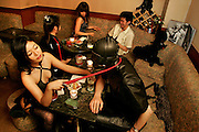 MUGEN - S&M Hostess Bar - Tokyo..Hostesses  with clients in hostess bar MUGEN (in Roppongi). Mugen is owned by Hige who is like a rope prodigy with over 2 decades of experience in ties, and quick releases and teaches all the women that work there tricks of the trade.