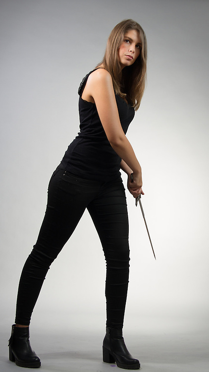 Female model posing in a contemporary outfit with a sword.