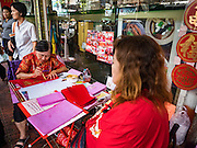 18 JANUARY 2017 - BANGKOK, THAILAND: A traditional Chinese calligrapher draws New Years greetings that she sells in Bangkok's Chinatown district, before the celebration of the Lunar New Year. Chinese New Year, also called Lunar New Year or Tet (in Vietnamese communities) starts Saturday, 28 January. The coming year will be the &quot;Year of the Rooster.&quot; Thailand has the largest overseas Chinese population in the world; about 14 percent of Thais are of Chinese ancestry and some Chinese holidays, especially Chinese New Year, are widely celebrated in Thailand.<br />       PHOTO BY JACK KURTZ