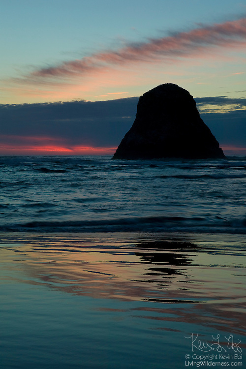 A large sea stack is partially reflected in the sand at Ecola State Park, near Cannon Beach, Oregon.
