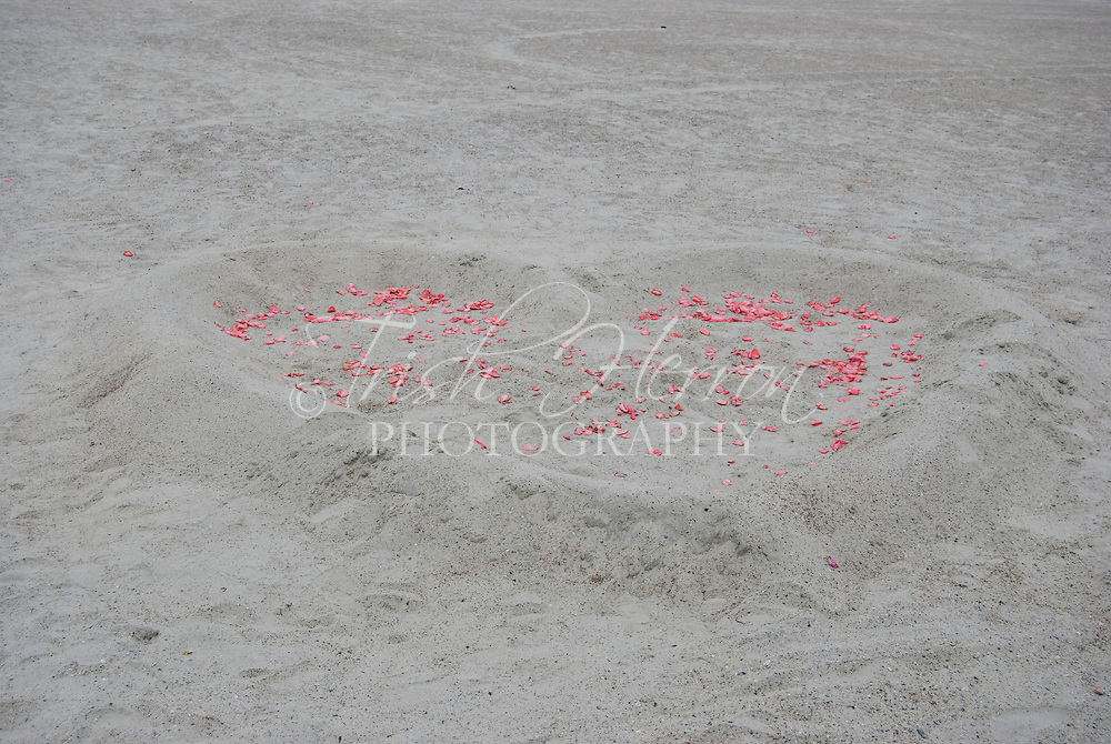 A heart constructed of sand and scattered with rose petals waits for a wedding on the beach in St. Augustine Beach, Florida.