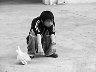Chinese boy sitting in a typical pose on a bus stop, somewhere in Zhond Dien county, Yunnan, China.