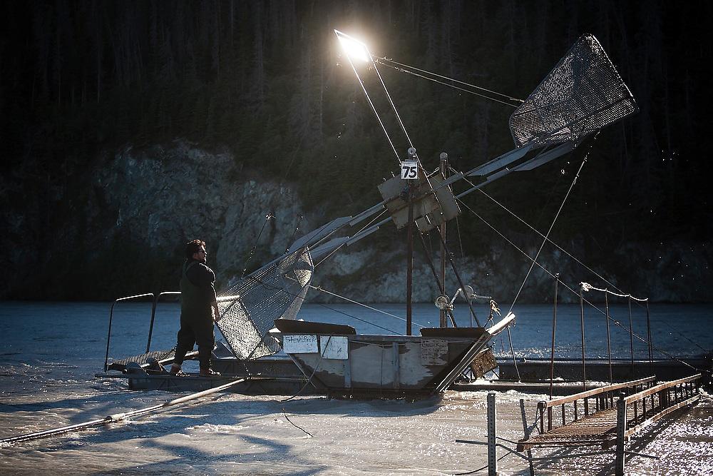 Carlos Rivera, from Wasilla, works on his family's fish wheel on the Copper River, near Chitina, Alaska.