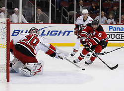 Oct 17, 2009; Newark, NJ, USA; Carolina Hurricanes goalie Cam Ward (30) makes a poke check save on New Jersey Devils left wing Zach Parise (9) during the second period at the Prudential Center.