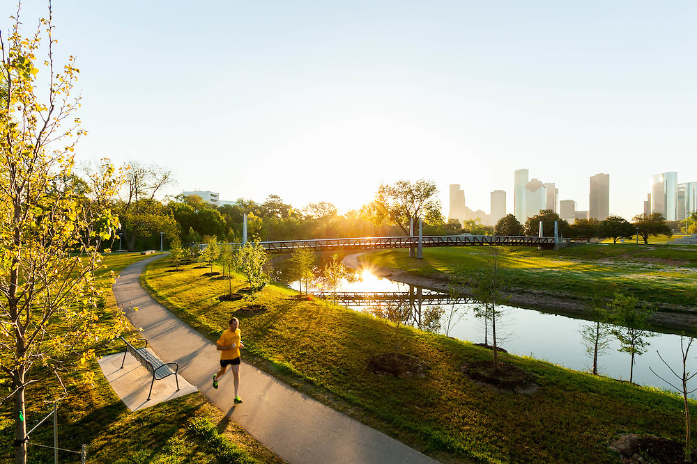 Jogger running on Buffalo Bayou Hike and Bike Trail with Houston, Texas skyline background.