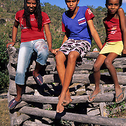 Country girls sitting on corral fence, Chapada da Piteira, Brazilian Highlands, Goias, Brazil