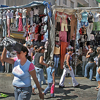"""Buhoneros - Pedestrians pass buhoneros' stalls filled with goods in the Sabana Grande neighborhood of Caracas Friday, December 15, 2006.  Buhoneros, thousands of workers who sell products from clothing and accessories to household goods and bootleg DVDs, make up the controversial """"informal economy.""""  While many Caracas residents complain that the buhoneros have taken over streets with their makeshift marketplace, many buhoneros give thanks to Venezuelan President Hugo Chavez for allowing them a way to survive by creating their own small businesses."""