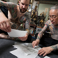 Horiyoshi III (the 3rd) (right of pic), expert Japanese tattooist, examine preliminary skecthes of tattoos with his German understudy Alex Reinke (also known as Horikitsune) (left of pic, with beard), in Horiyoshi's studio in Yokohama, Japan, on Saturday 10th September 2011.