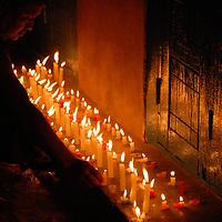 A monk lights candles outside a doorway on an auspicious Buddha day on the Tibetan Calendar in Kathmandu, Nepal.