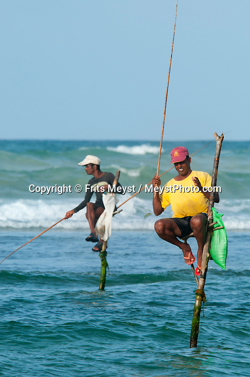 Matara, Sri Lanka, September 2011. Sri Lanka is known for its stilt firshermen. The fishermen sit on a cross bar called a petta tied to a vertical pole planted into the coral reef. They hold the stilt with one hand while fishing with a rod or line using the other. They're hoping to catch spotted herrings (koraburuwa) and small mackerels (bolla), which are stored in a plastic bag tied around their waist or the pole. The poles are 3-4 m long and driven about half a metre into the reef, so the fishermen sit at a height of about 2 m.  Photo by Frits Meyst/Adventure4ever.com