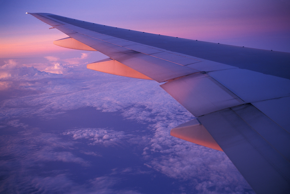 Asia, Thailand, Setting sun lights wing of Thai Airlines jet flying over storm clouds north of Bangkok