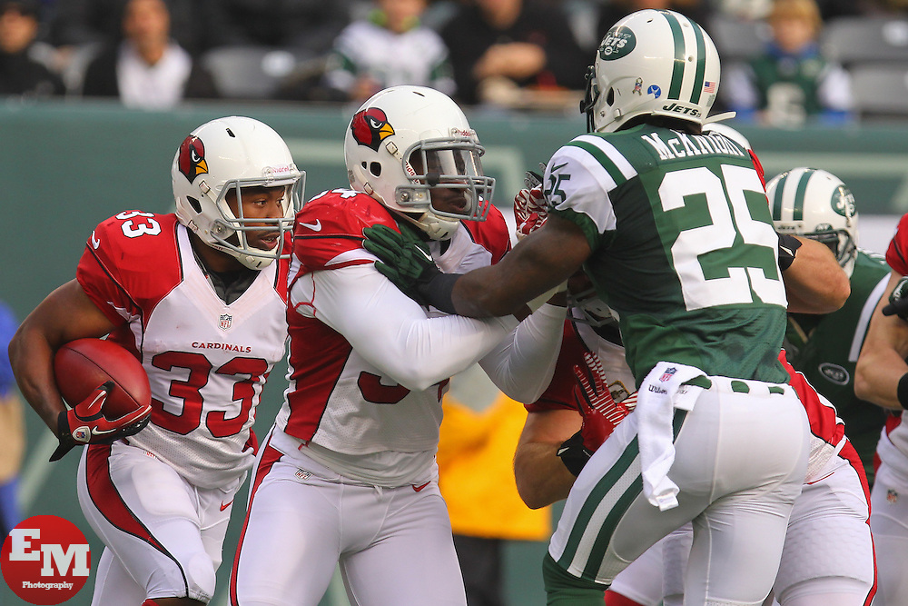 Dec 2, 2012; East Rutherford, NJ, USA; Arizona Cardinals running back William Powell (33) returns the opening kickoff while being pursued by New York Jets running back Joe McKnight (25) during the first half at MetLIfe Stadium.