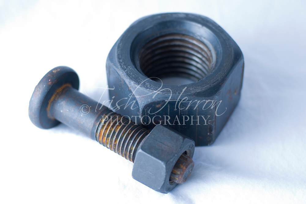 A bolt with small nut attached next to a large hexagonal nut.