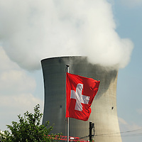 Swiss flag and the cooling tower of Leibstadt nuclear power station, with the top of the dome of the reactor is just visible at left. One of four sites in Switzerland, this plant stands close to the German border.<br /> The Swiss are due to vote shortly in a referendum whether to quit nuclear power, which via its five reactors, on four sites, provide almost 40% of the country's power