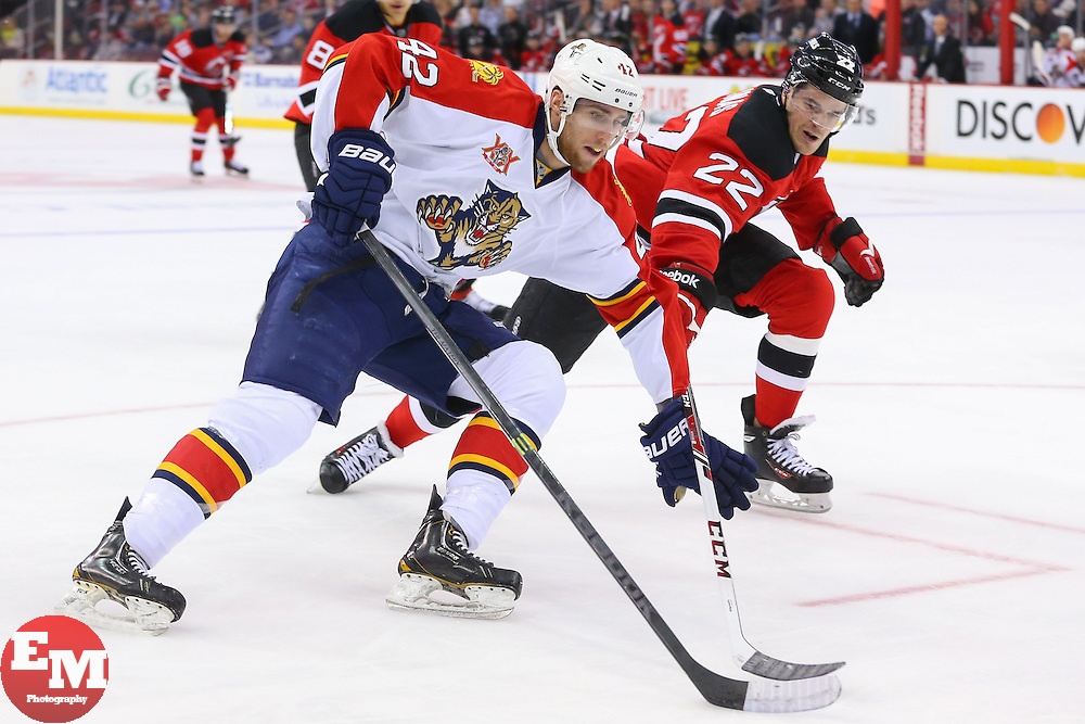 Mar 31, 2014; Newark, NJ, USA; Florida Panthers center Quinton Howden (42) protects the puck from New Jersey Devils defenseman Eric Gelinas (22) during the second period at Prudential Center.