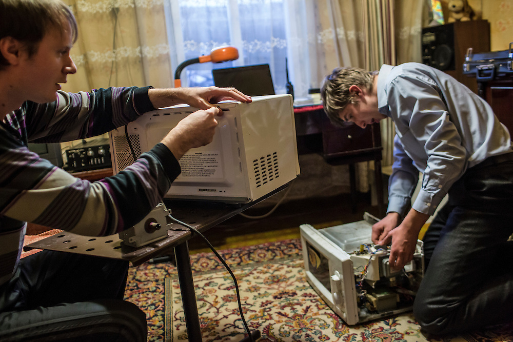 LUHANSK, UKRAINE - MARCH 15, 2015: Aleksandr Kryukov, left, and Pavel Pavlov take apart microwave ovens to retrieve parts they will use for scientific experiments featured in their YouTube videos at Kryukov's grandmother's house in Luhansk, Ukraine. CREDIT: Brendan Hoffman for The New York Times
