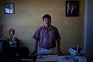 "A portrait of Francisco Valle Piamonte, mayor of San Mateo, a town feuding with Santa Maria, a town which has agreed to permit the construction of wind farms on disputed territory...The Isthmus of Tehuantapec, long a center for indigenous land ownership, is now embroiled in a land dispute over wind farm land...Called ""Mexico's little waist,"" the Isthmus is a wind tunnel that links the Gulf of Mexico to the Pacific through mountain passes at the narrowest part of Mexico. The geographical funnel makes it one of the windiest places in North America and for a decade wind energy companies have been jostling to acquire land to power the likes of Coca-Cola and Wal Mart."
