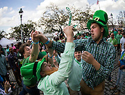 Chris Mitchum, left, and Joe Padgett, right, of Charleston, S.C. battle over beads tossed from a balcony during the start of a four-day St. Patrick's Day celebration Saturday, March 14, 2015, on River Street in Savannah, Ga. Thousands of gaudy green visitors are in Savannah this weekend to kick off the celebration that peaks Tuesday with the St. Patrick's Day parade. (AP Photo/Stephen B. Morton)