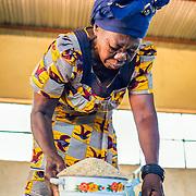LÉGENDE: Elle verse des grains de riz dans une petite marmite à l'intérieur de bassin. LIEU: Centre COFEMAK, Koumra, Tchad. PERSONNE(S): Responsable du moulin (à gauche).