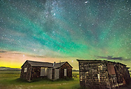 The Pleiades rising behind the rustic cabins and outbuildings of the historic Larson Ranch in Grasslands National Park, Saskatchewan. Aurora shines to the left in the north while green airglow illuminates the sky to the east above the buildings. Grasslands is a Dark Sky Preserve. And the sky is very dark. All illumination here is natural &mdash; note the dark clouds seen against the brighter airglow-lit sky. <br /> <br /> This is a stack of 4 exposures for the ground to smooth noise and one exposure for the sky, all untracked, and 30 seconds at f/2 with the 20mm Sigma lens and Nikon D750 at ISO 3200.