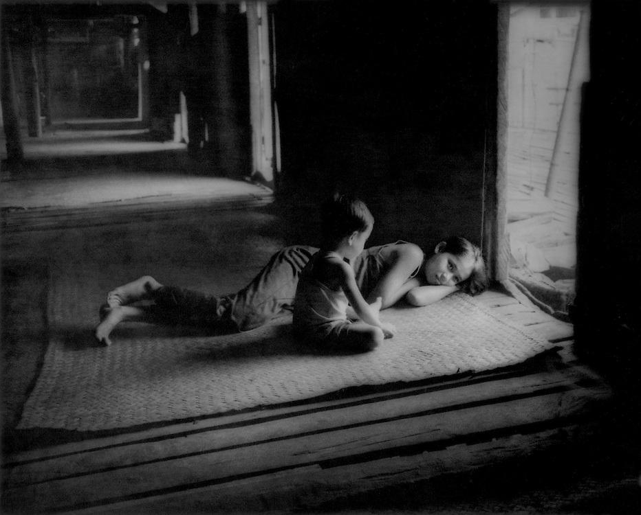 Young Iban Dayak mother lounges with her baby on the veranda of Nanga Sumpa longhouse, Sarawak, Malayasian Borneo.