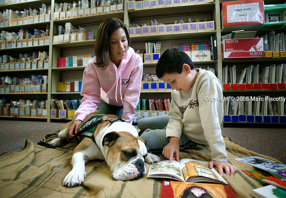 """4/11/08 11:14:14 AM -- Denver, CO. -- Ordinary dogs as therapy animals -- .Shannon Pryor (background), 29, of Wheatridge, Co. volunteers with 'Biscuit', her two year-old male English Bulldog as a therapy dog tandem every other Friday at Pine Grove Elementary School in Parker, Co. 'Biscuit' and Pryor work with special needs first grader Danny Connolly, 8, Parker, Co.  at the school helping him build confidence through handling and showing the dog off to classmates and working on reading skills as an understanding and sympathetic listener. The training required for this type of work is much less intensive than a service dog and therefore more accessible to many pet owners. Pryor said, """"I love volunteering and it makes you feel good inside helping kids"""". Danny (center) shows 'Biscuit' a picture in a kids book entitled """"Sit, Truman!"""" that he was reading to 'Biscuit' and Pryor..(Photo by Marc Piscotty / © 2008)"""