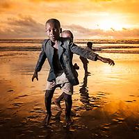 Crianças a brincarem alegres na praia de Fútila em Cabinda