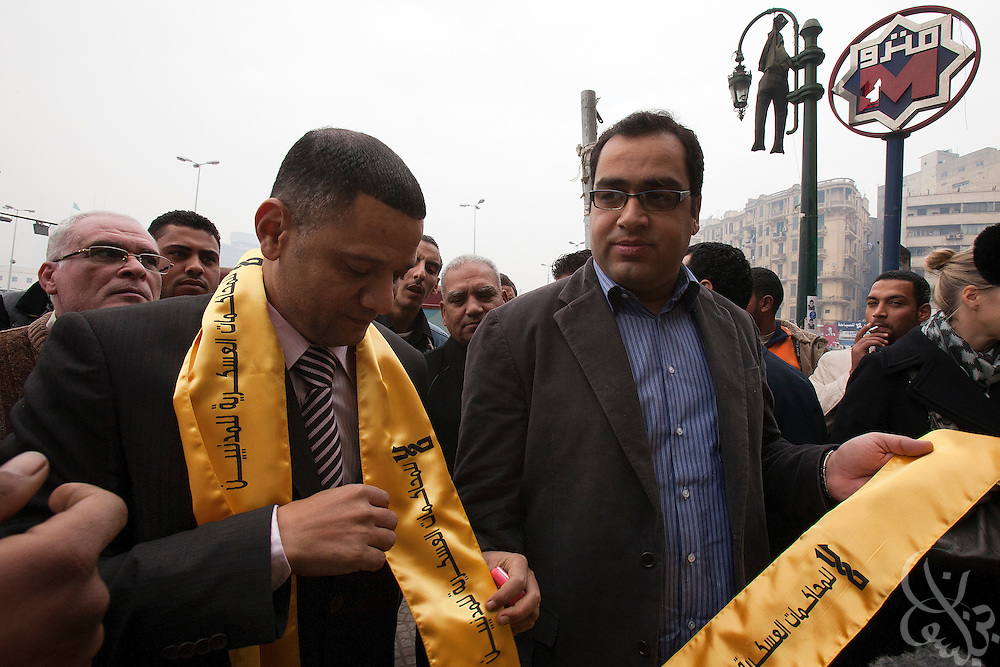 Egyptian Parliamentarian-elect Zyad Elelaimy (r) and Khalid Shabani show a group of journalists gathered in Tahrir Square the protest sashes they will wear inside the historic first session of Egypt's newly elected Parliament session Jan 23, 2012.