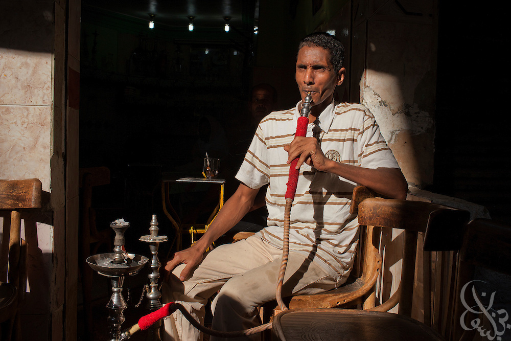 Egyptian worker Ahmed, smokes a water pipe in a coffee shop in the working class Cairo neighborhood of Imbaba July 16, 2011. Ahmed says crime has risen since the revolution in his neighborhood, saying criminal gangs and unemployed youth battle there daily.  (Photo by Scott Nelson)
