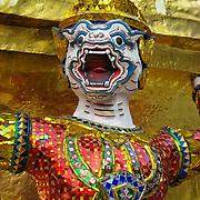 """A demon guards a gilded chedi (or stupa) at the Temple of the Emerald Buddha (Wat Phra Kaew), which is a shining complex of buildings within the grounds of the Grand Palace in Bangkok, Thailand. The Grand Palace (or Phra Borom Maha Ratcha Wang, in Thai) was built on the east bank of the Chao Phraya River starting in 1782, during the reign of Rama I. It served as the official residence of the king of Thailand from the 1700s to mid 1900s. Photo by Carol Dempsey. Published in """"Light Travel: Photography on the Go"""" by Tom Dempsey 2009, 2010."""