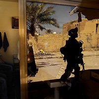 U.S. Army Pvt. 1st Class David Banks is eyed by locals as he walks past a barber shop during a cordon and search in Old Baqubah, Iraq, on April 4, 2007. Photo by Stacy L. Pearsall