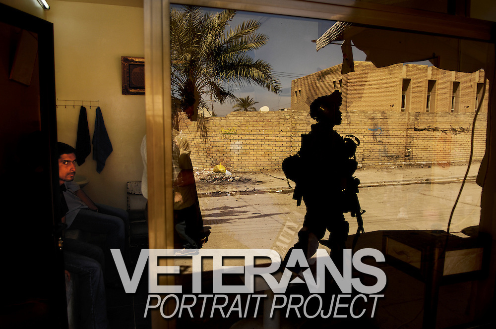 U.S. Army Pvt. 1st Class David Banks is eyed by locals as he walks past a barber shop during a cordon and search in Old Baqubah, Iraq, on April 4, 2007.