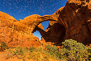 The famous and photogenic Double Arch at Arches National Park in Utah, shot in moonlight with illumination from a rising waning gibbous Moon on April 6, 2015. <br /> <br /> This is a stack of 4 x 40 second exposures at f/4 and ISO 1600 with the Canon 24mm lens and Canon 6D, to provide short star trails from stars in the northern sky.