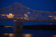 At dusk, a tank truck speeds over the Murray Baker Bridge on I-74 in Peoria, IL.