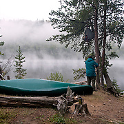 Taking down the food pack that hangs from a tree at base camp in the Boundary Waters in Northern, Minnesota.