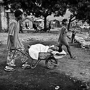 The number of cholera victims in CitÈ Soleil, a slum of Port-au-Prince, is increasing day by day exponentially, according to a doctor of Doctors Without Borders.///Jean-Pierre Britus and Janette Jackson carry their mother in a wheelbarrow, Kernilis St Jean, who suffered from cholera, to the nearest hospital, in the slum of Cite Soleil in Port-au-Prince.