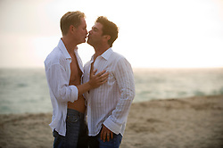 Two men on the beach kissing