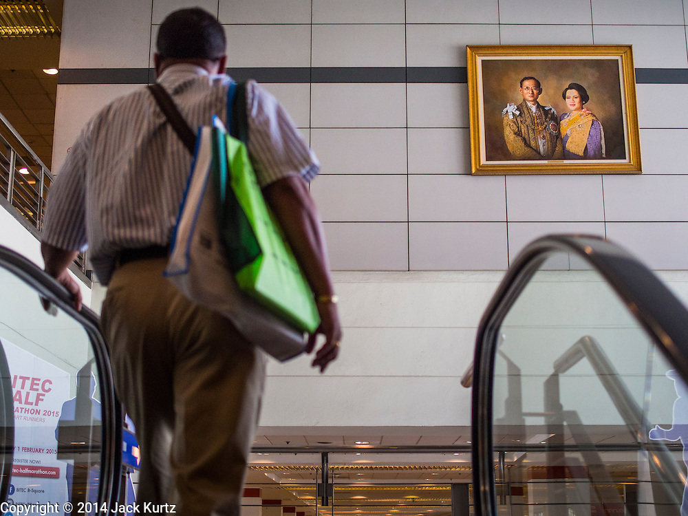27 NOVEMBER 2014 - BANGKOK, THAILAND:  A man rides an escalator past a portrait of Bhumibol Adulyadej, the King of Thailand, and his wife, Queen Sirikit in the BITEC Conference center in Bangkok. Pictures of the King are prominently displayed in most public buildings in Thailand. Bhumibol Adulyadej, the King of Thailand, was born on December 5, 1927, in Cambridge, Massachusetts. The family was in the United States because his father, Prince Mahidol, was studying Public Health at Harvard University. He has reigned since 1946 and is the world's currently reigning longest serving monarch and the longest serving monarch in Thai history. Bhumibol, who is in poor health, is revered by the Thai people. December 5, his birthday, is a national holiday and is also celebrated as Father's Day. The King is currently hospitalized in Siriraj Hospital, recovering from a series of health setbacks.      PHOTO BY JACK KURTZ