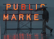 The sudden dark of a late-afternoon shower is broken by Seattle's landmark Pike Place Market sign. (Steve Ringman / The Seattle Times)