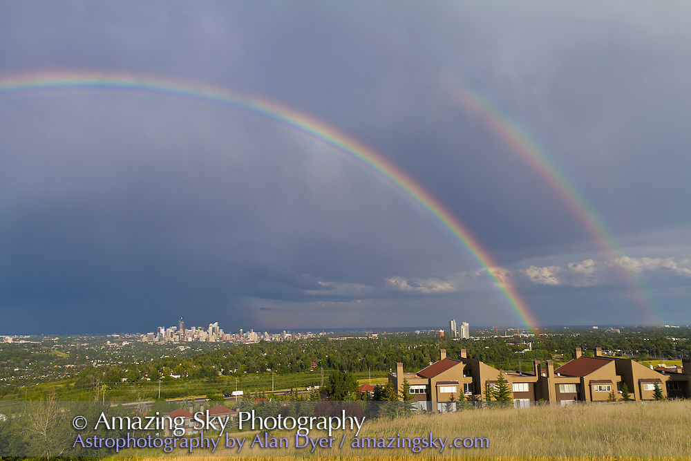 Rainbow over Calgary skyline, shot from park behind CFCN Broadcast building on Coach Hill, west end of Calgary, looking east at a receding thunder and hail storm which had dropped torrential rain and large hail over much of Calgary in the preceding hour. Notice supernumerary arcs inside main bow. Shot with Canon 7D and Canon 10-22mm lens.