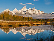 """Lenticular clouds (lens or wave clouds) cap the peaks of Grand Teton (13,766 feet or 4198.6 meters) and Teewinot. The Teton Range reflects in the Snake River at Schwabacher Landing in Grand Teton National Park, Wyoming, USA. Grand Teton National Park contains the major peaks of the 40-mile (64 km) Teton Range and part of the valley known as Jackson Hole, Wyoming. The Teton Range began their tectonic uplift 9 million years ago (during the Miocene Epoch), making them the youngest range in the Rocky Mountains. A parkway connects from Grand Teton National Park 10 miles north to Yellowstone National Park. Published in the book """"Mountain"""" by Sandy Hill, 2011, Rizzoli International Publications Inc (p. 103), a benefit for the American Alpine Club Library."""