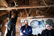 Zbigniew Nawrot stretches while restless scientists Grzegorz Gajek (center) and Piotr Zagorski wait out high winds in the comfort of the Polish field station in Calypsobyen, Svalbard.