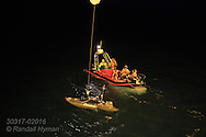 Motorized kayak laden with high-tech equipment for measuring imperceptible light changes of high noon during polar night hangs from cable beside RV Helmer Hanssen as scientists guide it into water in January in Kongsfjorden, Svalbard, Norway.