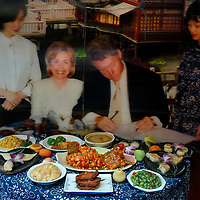Restaurant's display window, of prepared dishes in front of a blown-up photo of when it was visited by President Clinton...From China [sur]real © Mark Henley..