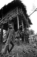 young kombai child and women outside  their tree house