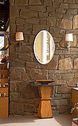 Stone wall bath sink with wood pedestal and oval mirror