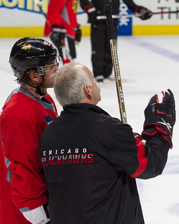 Chicago Blackhawks Coach Joel Quenneville speaks to forward Viktor Stålberg during a practice at the United Center December 29, 2011.