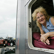 "Mickey McGregor, from Mesquite, Tx., peers out from her truck at the Truckers Jamboree held in Walcott, Iowa, every year.  This event was in 2006.   McGregor has been on the road with her husband since 1974.  Her husband has been driving since 1957.  ""After the last child got married (McGregor had 13 children), Dad told the kids that mom was going to be a wife again and learn to drive a truck,""  McGregor said.  McGregor called the truck they drive a ""junkyard dog"" because it is a combination of three different trucks."