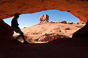 UT00103-00...UTAH - Hiker at Eye Of The Whale Arch in Arches National Park.